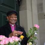 «Eine Rose aus Tanzania zugunsten der Projekte der Ökumenischen Kampagne»: Bischof Joseph Seoka aus Südafrika unterstützt das Verkaufsteam der Rosenaktion 2016 vor der Heiliggeist-Kirche in Bern.   ©Brot für alle / Urs Walter