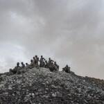 Eine Gruppe Kleinschürfer in der Goldmine Alga in Burkina Faso gönnt sich eine Pause auf einem Schutthaufen. (Foto: Meinrad Schade/Fastenopfer)