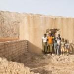 Eine Familie in Burkina Faso vor ihrem zerstörten Haus: Wegen dem Bau der Bissa-Goldmine wurde das ganze Dorf umgesiedelt. Im Hintergrund die Abraumhalde der Goldmine Bissa. (Foto: Meinrad Schade/Fastenopfer)