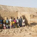Eine Familie vor einem zerstörten Haus