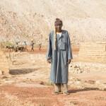 Ein Bauer in Burkina Faso den Ruinen seines zerstörten Hauses: Wegen dem Bau der Bissa-Goldmine wurde das ganze Dorf umgesiedelt. Im Hintergrund die Abraumhalde der Goldmine Bissa. (Foto: Meinrad Schade/Fastenopfer)
