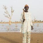 Ein Bauer mit Werkzeug vor einem See.