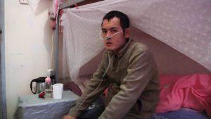 Mann mit Atemschläuchen auf seinem Bett.