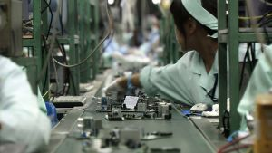 Arbeiterinnen am Fliessband in einer Produktionshalle für Elektonikprodukte.