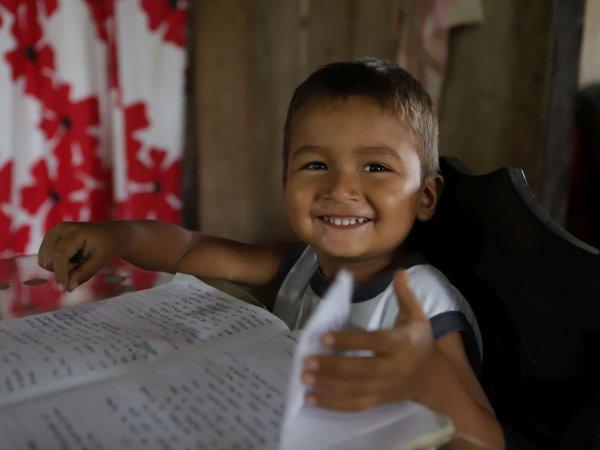 Junge aus Kolumbien, der am Tisch sitzt und lernt. Aus der Projektarbeit von Fastenopfer.